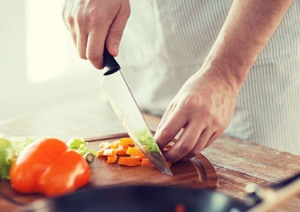 cooking, food and home concept - close up of male hand cutting p