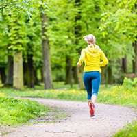 Woman runner running with dog in park summer nature exercising in bright forest outdoors