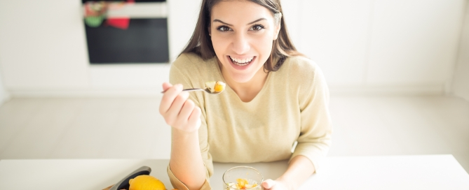 Healthy looking cheerful woman eating homemade organic fruit mix fruit salad.Fruit diet,dieting,nutrition,vegetarian concept.Food for better skin,strong immune system,diet fitness meal.Healthy snack